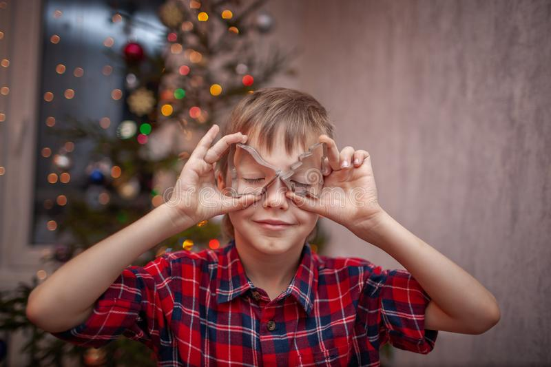Adorable little boy is preparing the gingerbread, bake cookies in the Christmas kitchen.  royalty free stock photo