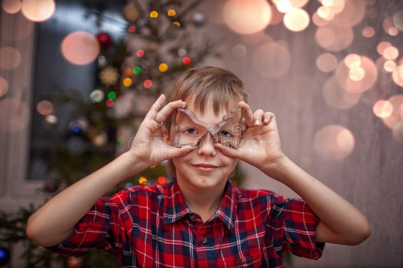 Adorable little boy is preparing the gingerbread, bake cookies in the Christmas kitchen.  stock photos