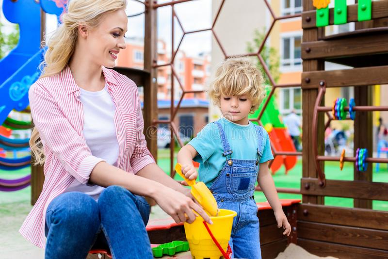 adorable little boy putting sand into bucket by plastic scoop while his mother holding bucket in sandbox stock photo