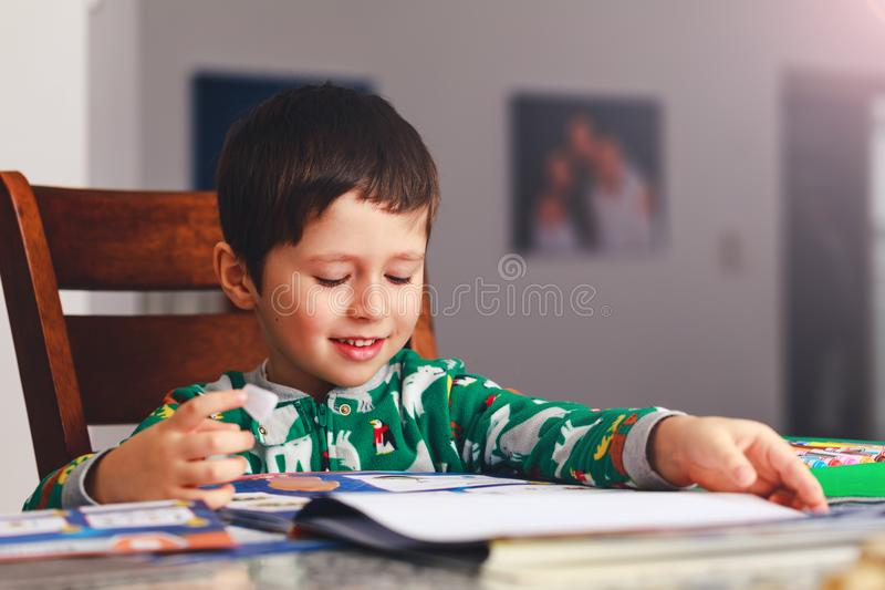 Adorable little boy reading book before going to sleep. Happy kid dressed in pajamas reads a story and amuses himself. Cute boy l stock image