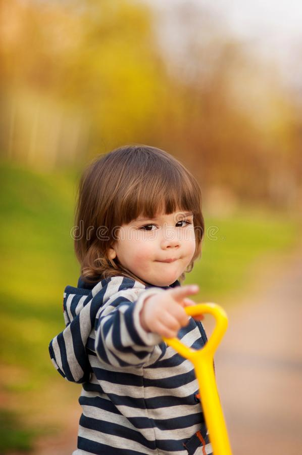Little boy walking on spring day playing with toys stock photos