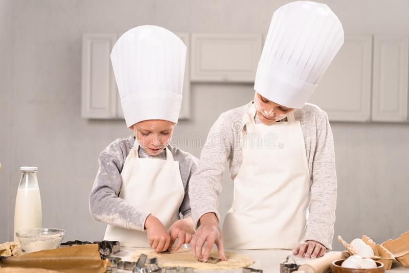 Adorable little brother and sister in chef hats and aprons cutting out dough for cookies at table. In kitchen royalty free stock images