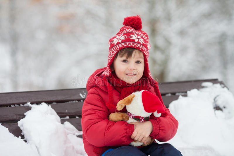 Adorable little child, boy, playing in a snowy park, holding ted stock photos