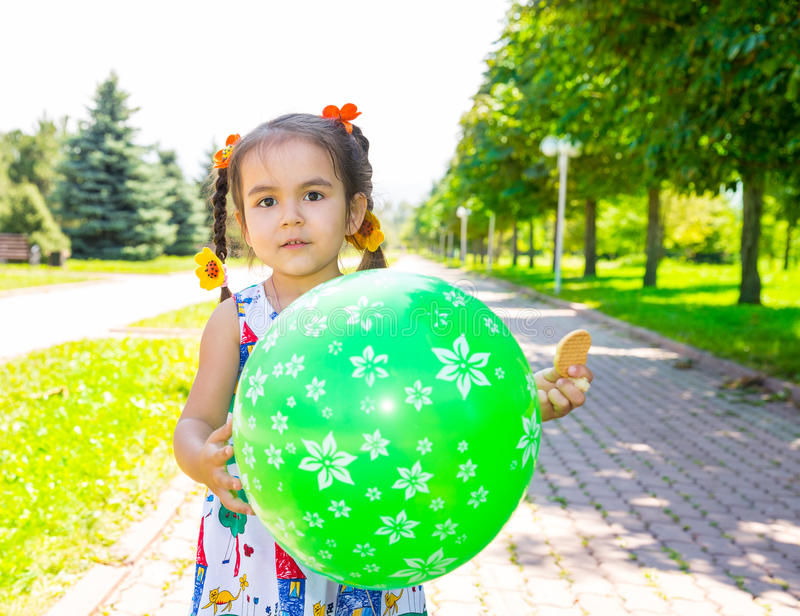 Adorable little child girl with balloons on summer nature background. stock photo