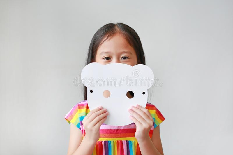 Adorable little child girl holding blank white animal paper mask fronting her face on white background. Idea and concept for kid. Dressed up playing animal face stock image