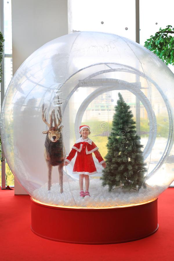 Adorable little child girl in santa costume dress playing in big winter Snow globe with reindeer on christmas time. Merry Xmas and. Happy new year royalty free stock image