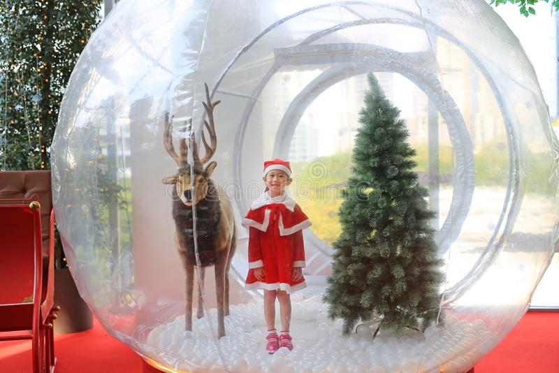 Adorable little child girl in santa costume dress playing in big winter Snow globe with reindeer on christmas time. Merry Xmas and. Happy new year royalty free stock photos