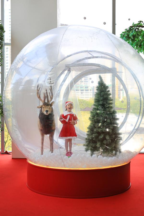 Adorable little child girl in santa costume dress playing in big winter Snow globe with reindeer on christmas time. Merry Xmas and. Happy new year stock photo