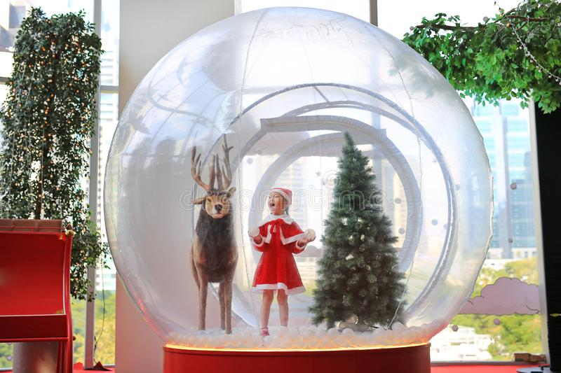 Adorable little child girl in santa costume dress playing in big winter Snow globe with reindeer on christmas time. Merry Xmas and. Happy new year stock photography