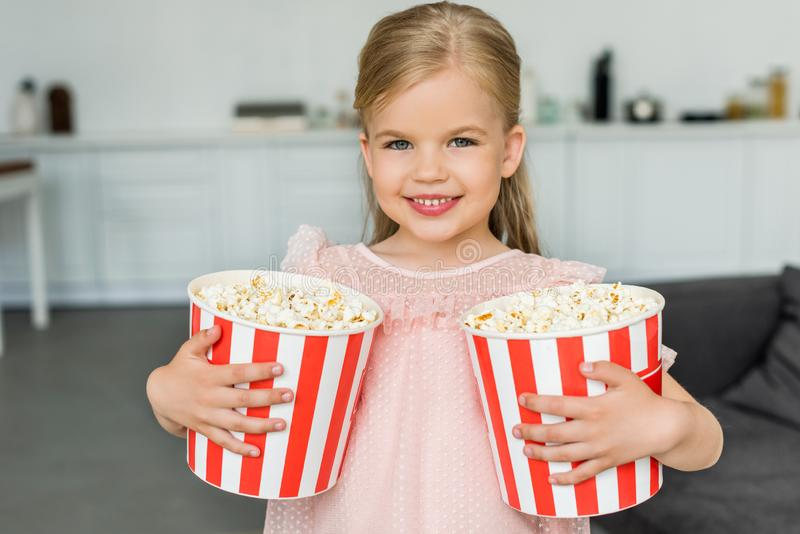 Adorable little child holding boxes with popcorn and smiling. At camera stock photography