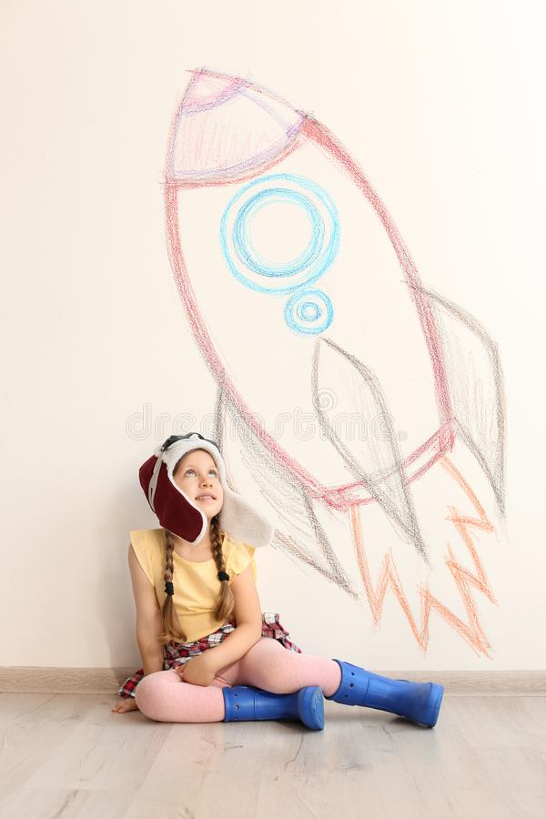 Adorable little child playing astronaut wall with drawing of spaceship indoors. Adorable little child playing astronaut near wall with drawing of spaceship stock images