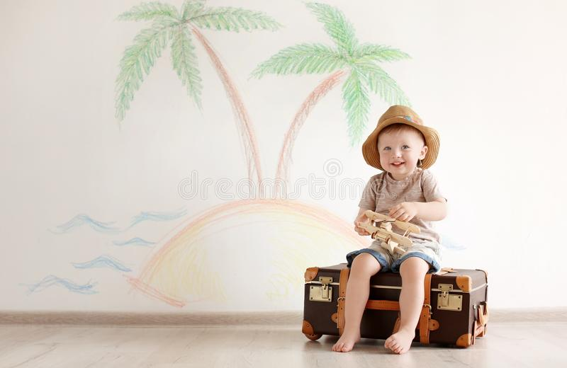 Adorable little child playing traveler with suitcase stock photography