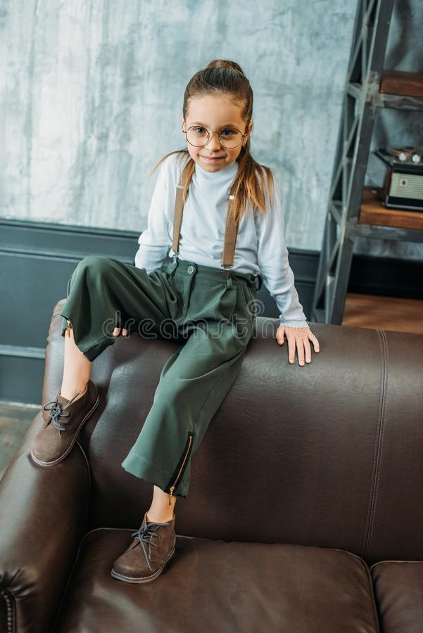 adorable little child in stylish clothing sitting on couch royalty free stock images