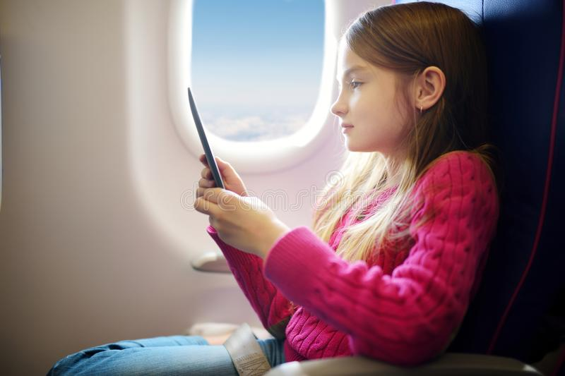 Adorable little child traveling by an airplane. Girl sitting by aircraft window and reading her ebook during the flight. Traveling. Abroad with kids stock photography