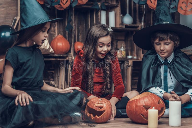 Adorable Little Children in Halloween Costumes. Cute Smiling Kids wearing Scary Halloween Costumes Sitting on Floor next to Carved Pumpkins and Candles. Cute royalty free stock photography
