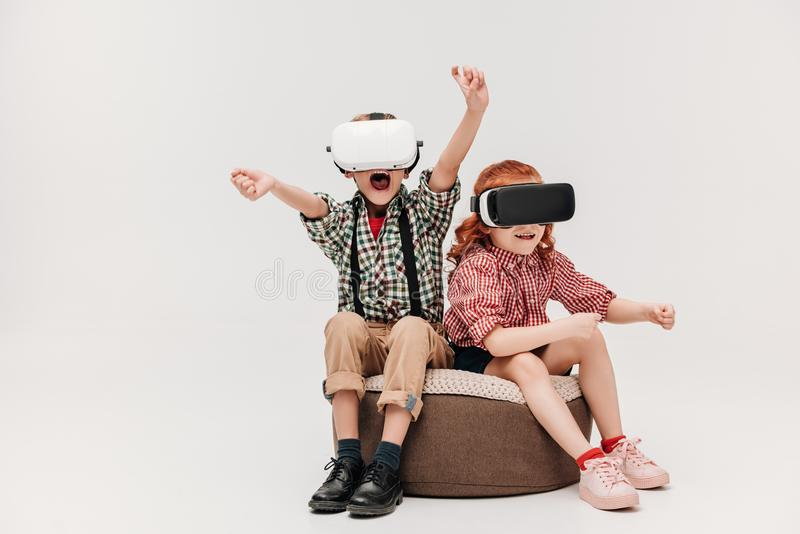 Adorable little children playing in virtual reality headsets. Isolated on grey royalty free stock photo