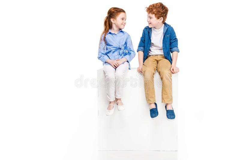 adorable little children sitting on white cube and smiling each other stock photo