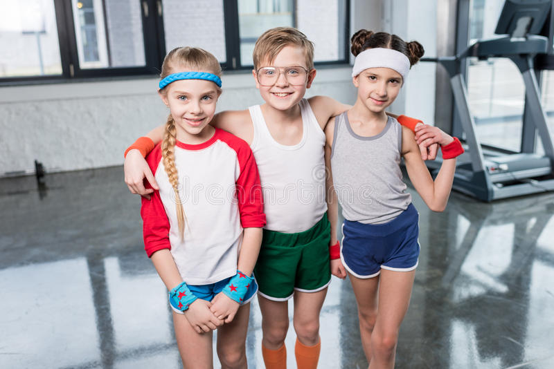 Adorable little children in sportswear standing embracing and smiling at camera in gym. Children sport school concept stock image