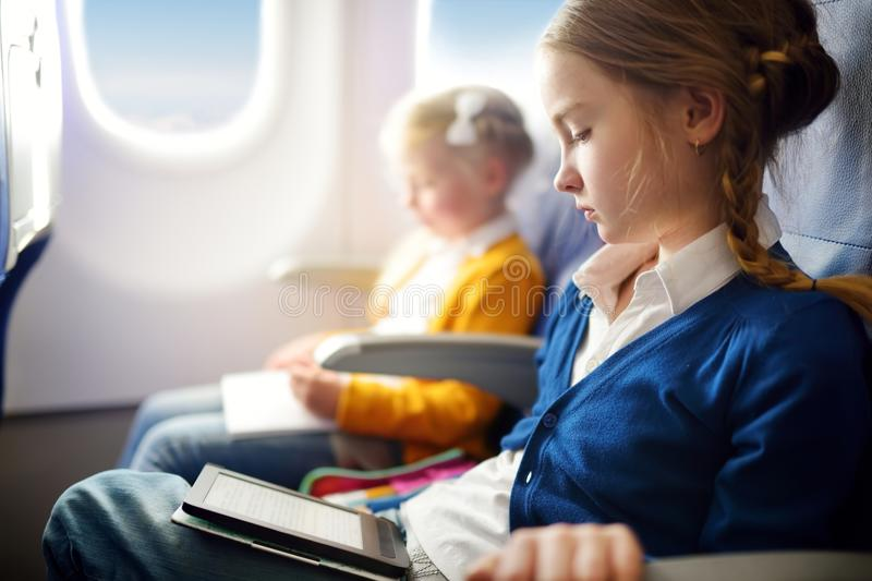 Adorable little children traveling by an airplane. Girl sitting by aircraft window and reading her ebook during the flight. Travel. Ing abroad with kids royalty free stock images