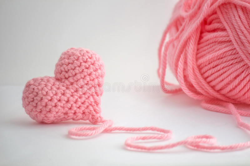 Adorable little crocheted heart and a skein of yarn stock image