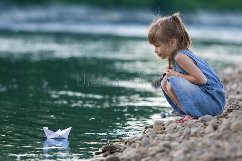 Adorable little cute blond girl in blue dress on riverbank pebbles playing with white paper origami boat on blue sparkling. Bokeh water background. Dreams and royalty free stock photo