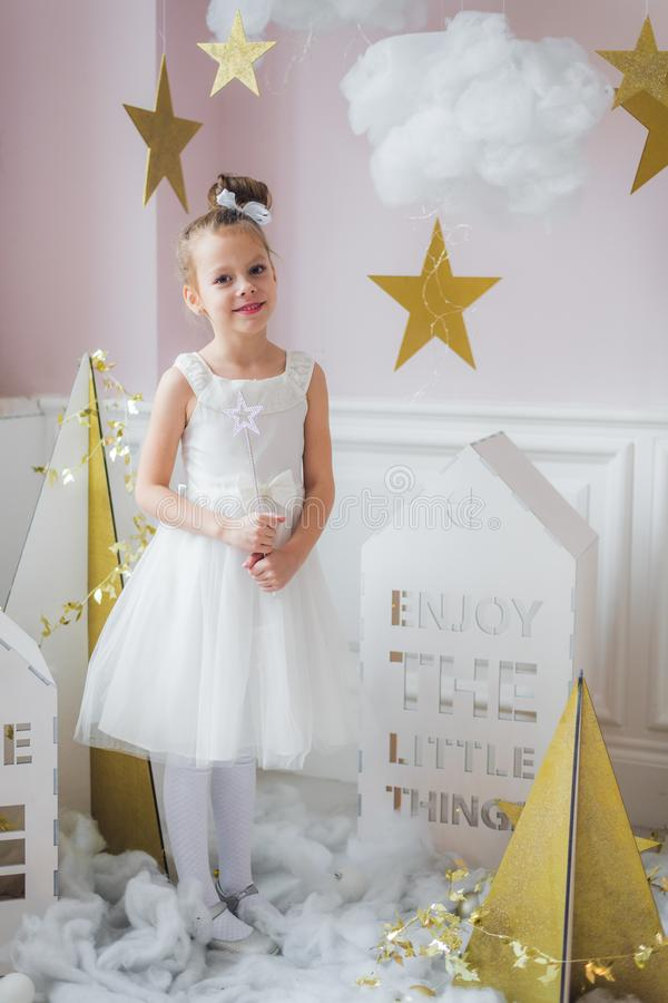 Adorable little fairy girl with magic wand at christmas decorations indoors royalty free stock photography