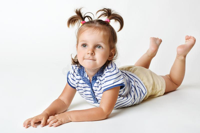 Adorable little female kid with attractive look, dreamy expression, has two funny pony tails, raises legs upwards, focused on some stock photography