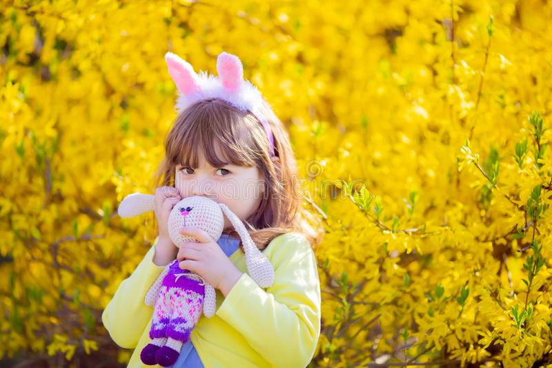 Adorable little funny bunny girl holding rabbit toy in the spring blossom garden stock images