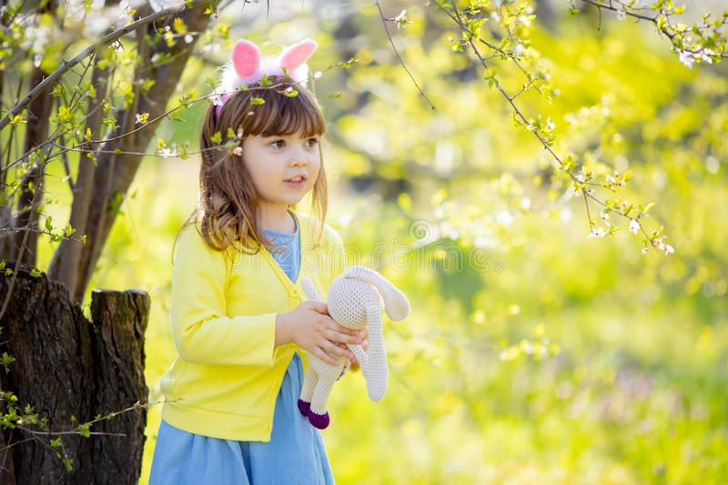Adorable little funny bunny girl holding rabbit toy in the spring blossom garden stock image
