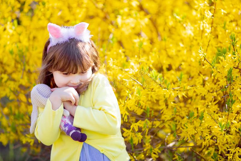 Adorable little funny bunny girl holding rabbit toy in the spring blossom garden stock photography