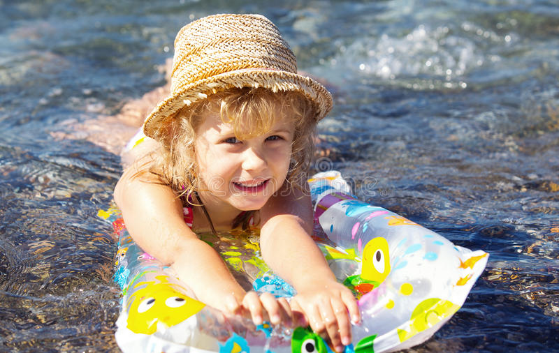 Adorable little girl on air inflatable mattress stock photo