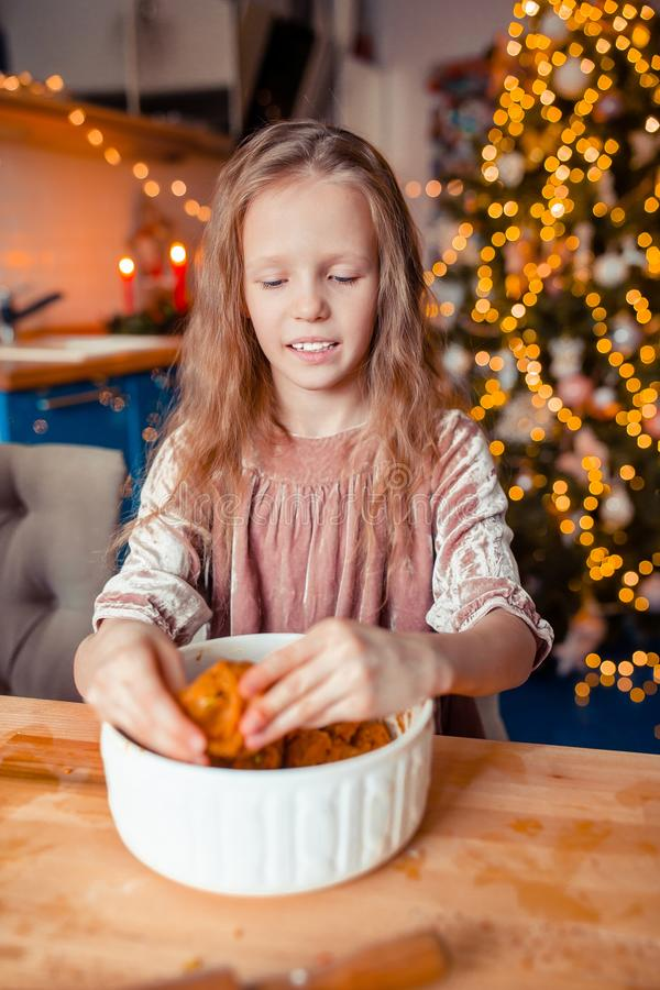 Adorable little girl baking Christmas gingerbread cookies. Adorable happy little girl baking Christmas gingerbread cookies royalty free stock image