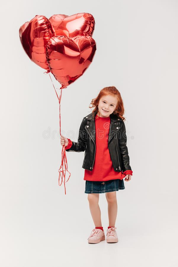 adorable little girl with balloons in shape of hearts royalty free stock photos