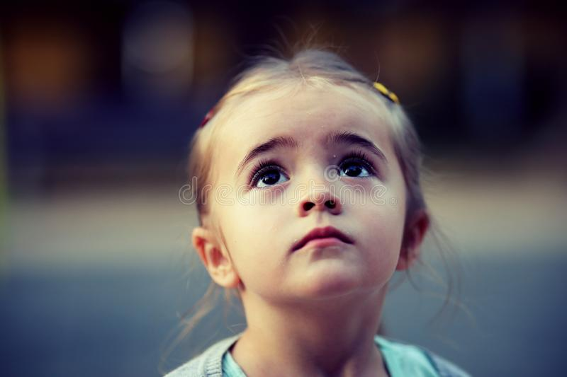 Adorable Little girl with beautiful blonde hair and big brown eyes daydreaming, watching the sky stock images