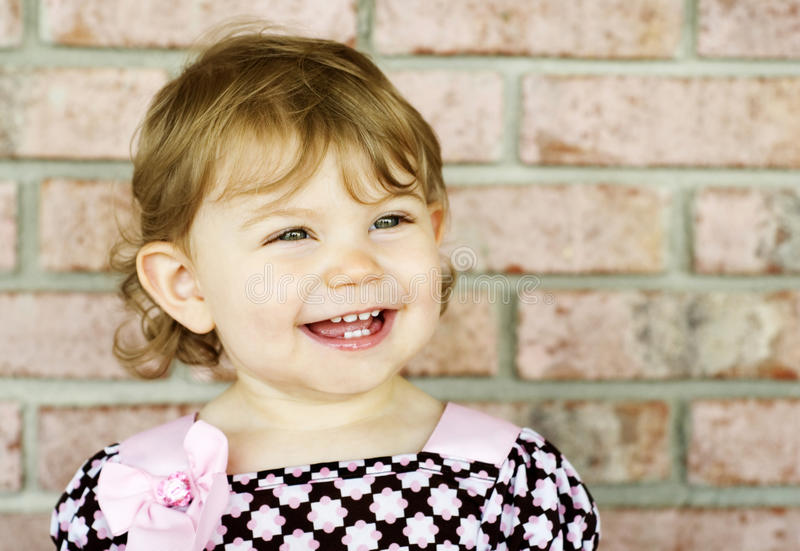 Adorable Little Girl Big Smile Bright Eyes. An adorable little girl with a big smile and bright eyes, brick wall background, shallow depth of field used with royalty free stock images