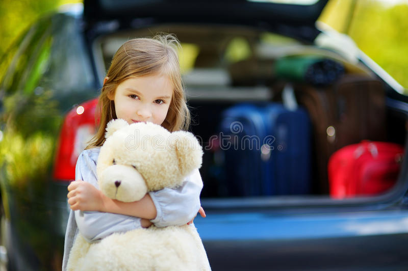 Adorable little girl with big teddy bear. Leaving for a car vacation with her parents stock photos
