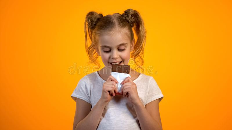 Adorable little girl biting delicious chocolate enjoying sweet taste happy child royalty free stock photography