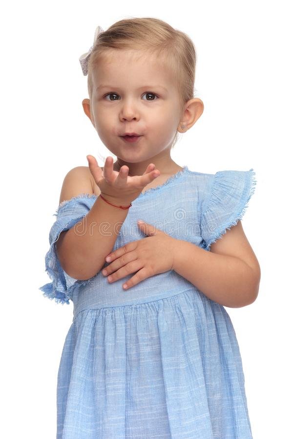 Adorable little girl in blue dress is blowing a kiss stock image