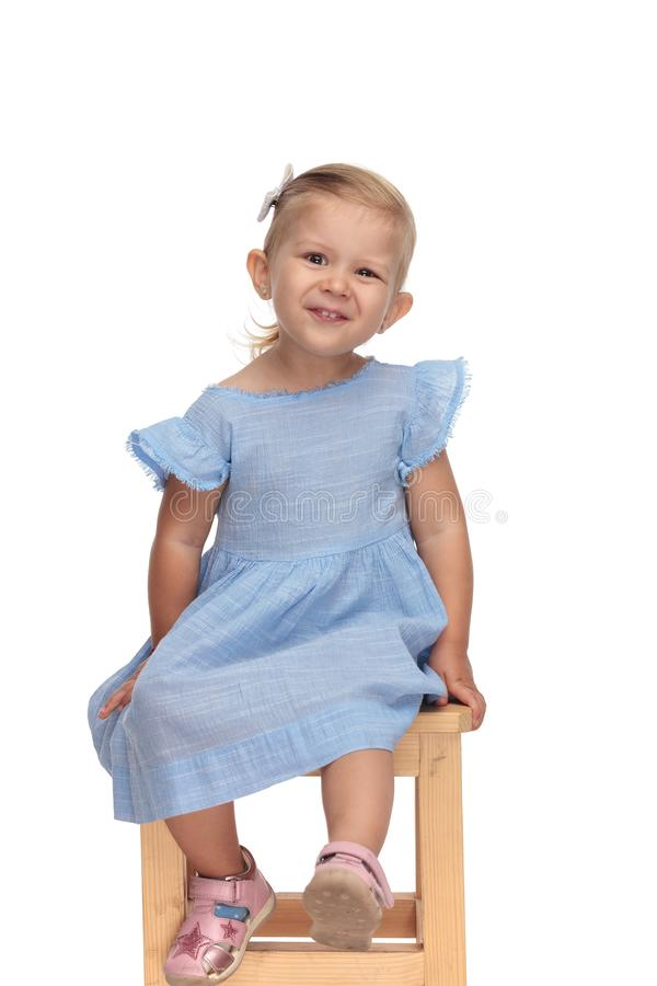 Adorable little girl in blue dress laughing and sitting chair stock image