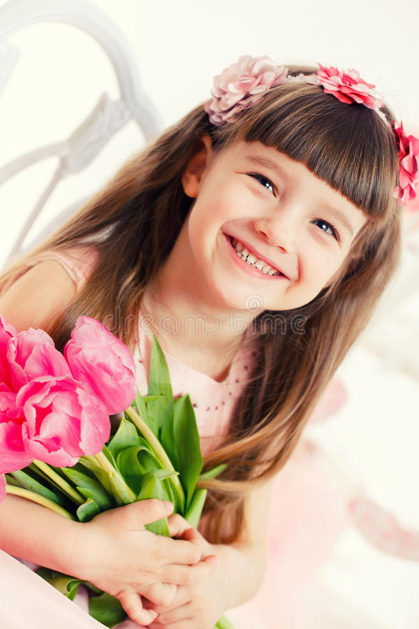 Adorable little girl with bouquet of tulips. Beautiful girl in a pink dress, sitting on a stool with a bouquet of tulips stock photography