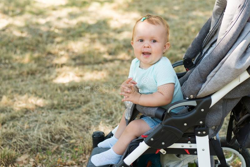 Adorable little girl in bright stylish clothes sitting in pushchair outdoors . Autumn walks with kids royalty free stock photo