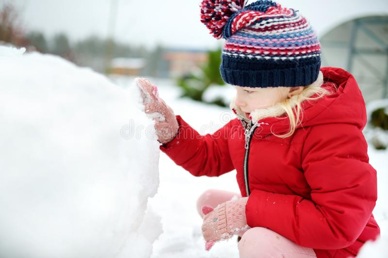 Adorable little girl building a snowman in the backyard. Cute child playing in a snow. stock photos