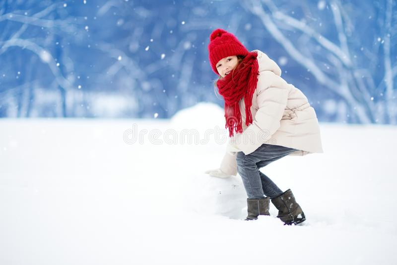 Adorable little girl building a snowman in beautiful winter park. Cute child playing in a snow. royalty free stock photo