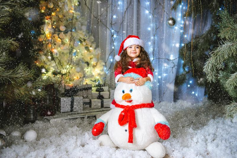 Adorable little girl building a snowman in beautiful winter park. Cute child playing in a snow. Winter activities for royalty free stock image