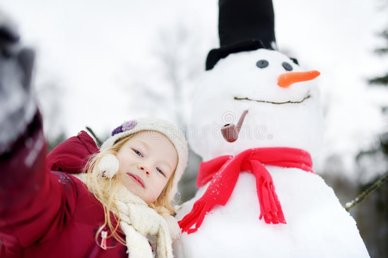 Adorable little girl building a snowman in beautiful winter park. Cute child playing in a snow. Winter activities for kids royalty free stock photo
