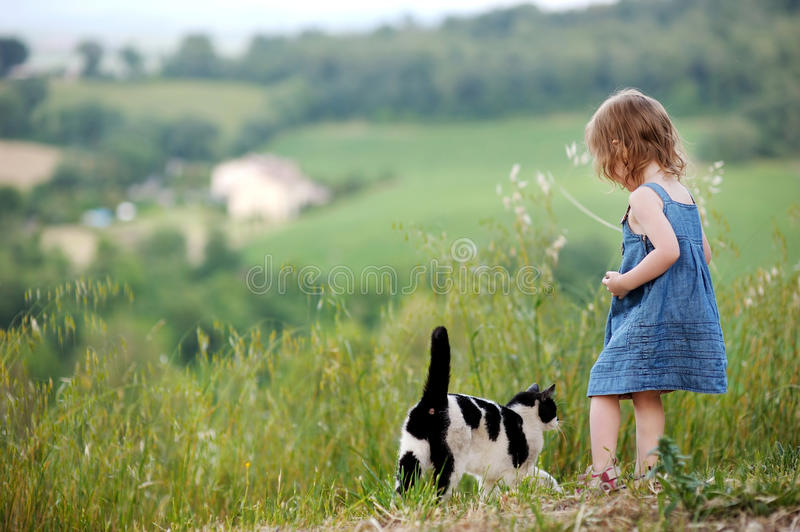 Adorable little girl and a cat. Outdoors stock image