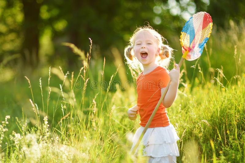 Adorable little girl catching butterflies and bugs with her scoop-net. Child exploring nature on sunny summer day royalty free stock photos