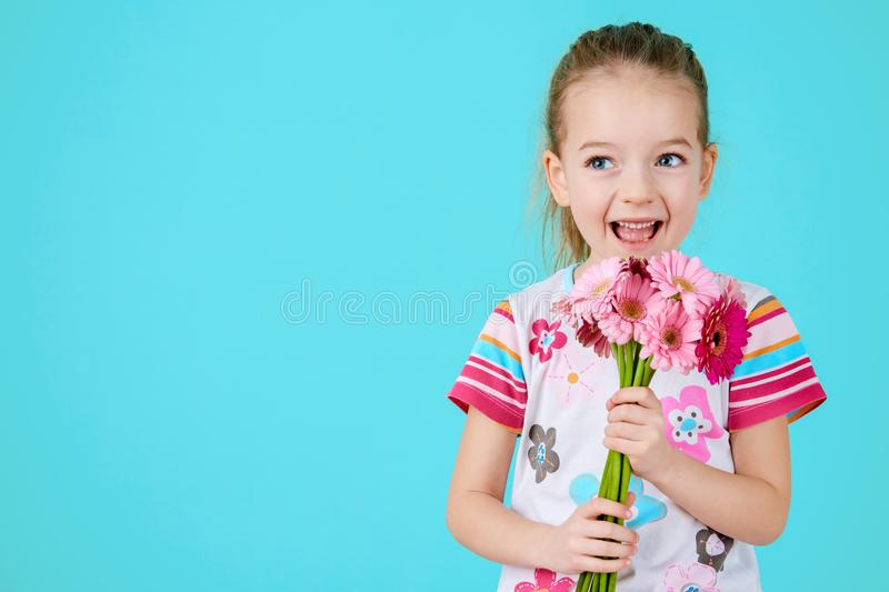 Adorable little girl with cheeky smile and face expression holding bouquet of pink gerbera daisies. Happy Mother`s Day. stock photo