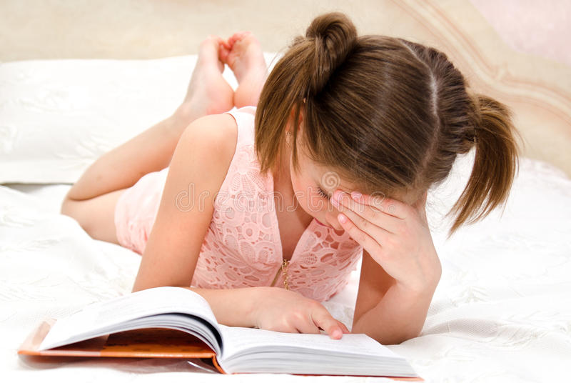 Adorable little girl child is reading a book stock photography
