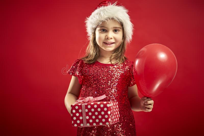 Adorable little girl in a Christmas dress in a Santa`s hat with a christmas gift royalty free stock photography